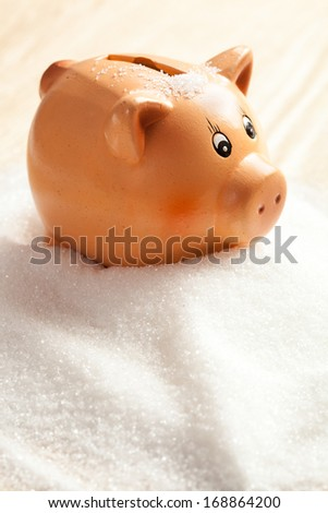 Piggy bank in a heap of white sugar - stock photo
