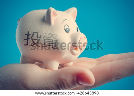 Piggy bank in a human hand with inscription INVESTMENTS on a blue background - stock photo