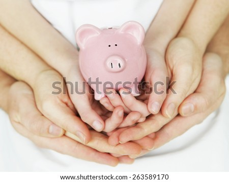 Piggy Bank in hands of a family - stock photo