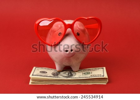 Piggy bank in love with red heart sunglasses standing on stack of money american hundred dollar bills on red background - stock photo