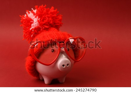 Piggy bank in love with red heart sunglasses with red hat and pom-pom standing on red background - stock photo