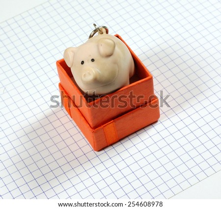 Piggy bank in the box on the notebook grid - stock photo