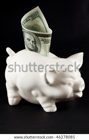 Piggy Bank isolated on black background with 100 bill - stock photo