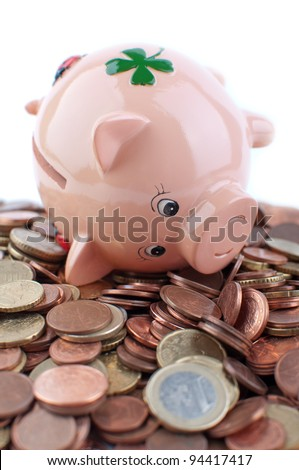 Piggy Bank lies on many european coins isolated on white - stock photo