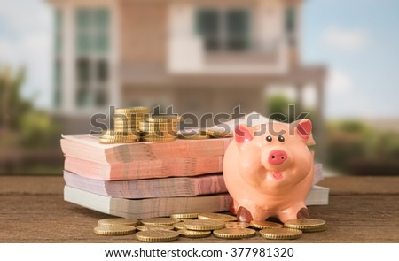 piggy bank , money with house in background. concept of savings plan, investment, loan, mortgage for house ,real estate ,residence. soft focus. - stock photo