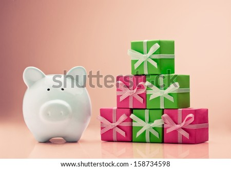 Piggy bank next to a gift boxes stack - stock photo
