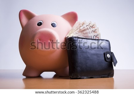 piggy bank old wallet with money - stock photo