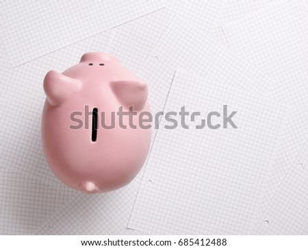Piggy bank on checked note pad paper with clipping path