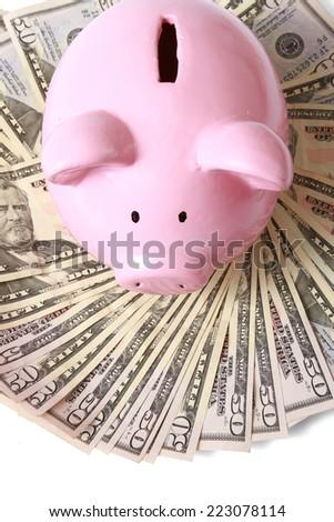 piggy bank on dollars, isolated on white background. - stock photo