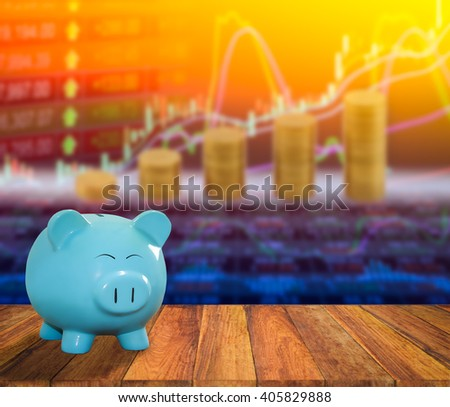 Piggy bank on empty wood table with stock market graph background. It's time to start saving for investment. That suitable for background,backdrop,wallpaper including your artwork design. - stock photo