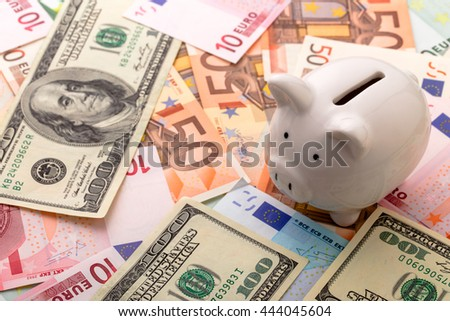Piggy bank on euro banknotes and dollars background - stock photo