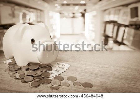piggy bank on pile of coins and banknote with blur shop background