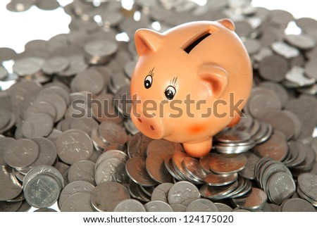 Piggy bank on pile of coins (lithuanian cents)  on white - stock photo