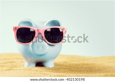 Piggy bank on sand. - stock photo