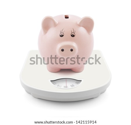 Piggy bank on scales - stock photo