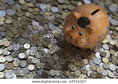 Piggy bank on sea of coins - stock photo