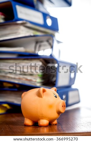 Piggy bank on table over stack of office folders. Shallow depth of field - stock photo
