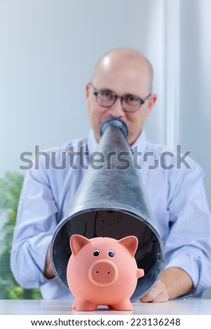piggy bank on the foreground and shouting man with a megaphone on the background with strong difference of focus