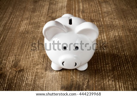 Piggy bank on the old wooden background, front view - stock photo