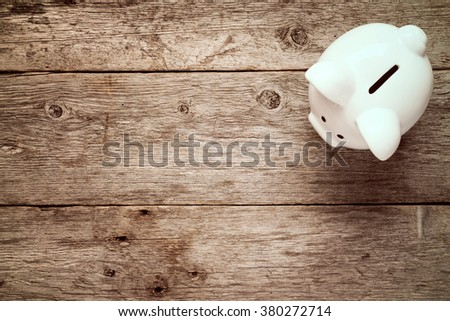 Piggy bank on the old wooden background, top view - stock photo
