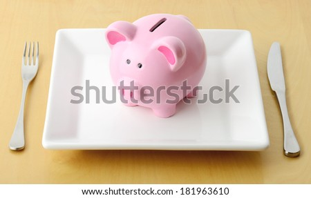 Piggy bank on the plate with fork and knife  - stock photo