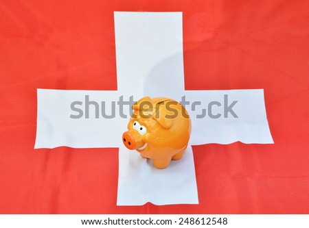 Piggy bank on the Swiss flag - stock photo