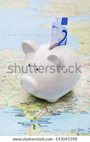 Piggy bank on top of a map symbol of world economy or holiday savings
