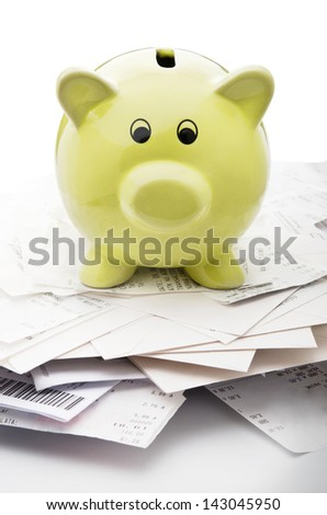 Piggy bank on top of stack of payed bills - stock photo