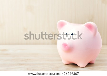 Piggy bank on wooden top table, money savings concept