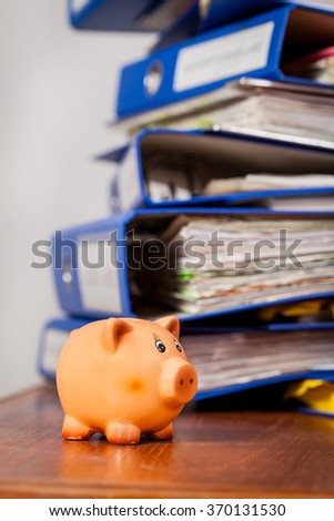Piggy bank over stack of office folders on background. Shallow depth of field - stock photo