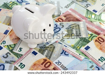 Piggy bank placed on Euro currency. Concept for cut in interest rates, euro crisis and saving