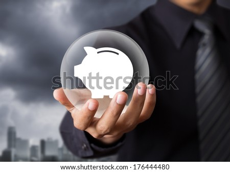 Piggy bank protected by crystal ball in hand - stock photo