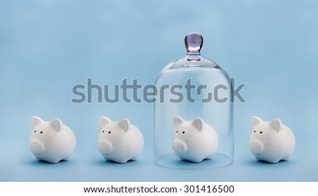 Piggy bank protected under a glass dome on blue background