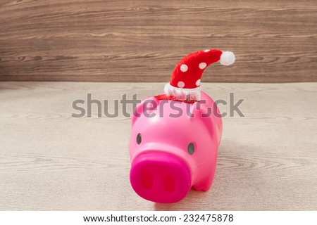 piggy bank ready for Christmas holiday on wooden background  , saving and financial concept.   - stock photo