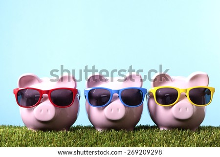 Piggy bank row, grass and blue sky, sunglasses, summer vacation concept  - stock photo