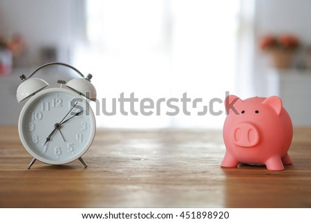Piggy bank save coin and alarm clock, time and money concept. copy space on center. - stock photo