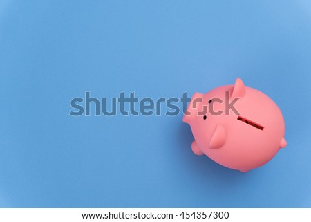 piggy bank save coin, blue desk background, copy space on Left side - stock photo