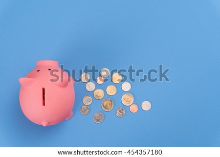 piggy bank save coin, blue desk background, top view. - stock photo