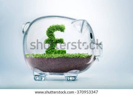 Piggy bank savings concept with grass growing in shape of British Pound