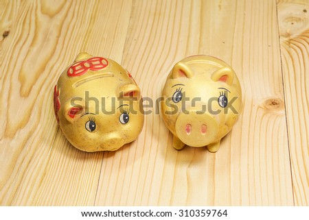 Piggy bank shaped like pig slop and two gold stain on brown wooden boards . - stock photo
