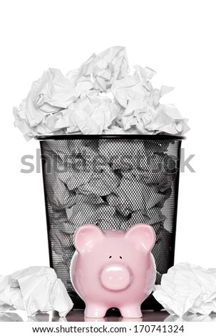 Piggy bank standing in front of the trash can - stock photo