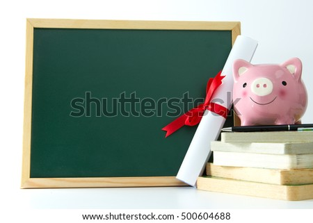Piggy bank standing on a stack of books next to blank blackboard, with copy space