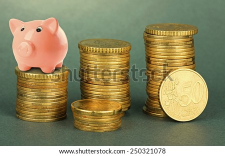 Piggy bank standing on stack of coins on gray background - stock photo