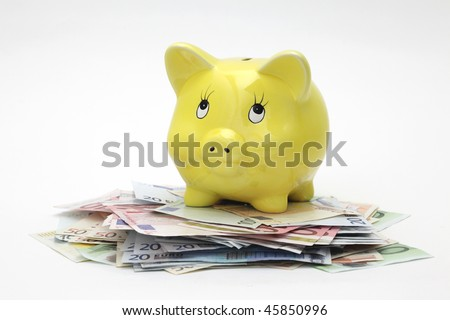 Piggy bank standing on top of Euro banknotes, isolated on white background - stock photo