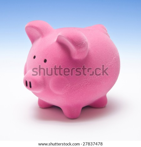 Piggy bank style money box on a graduated blue studio background.