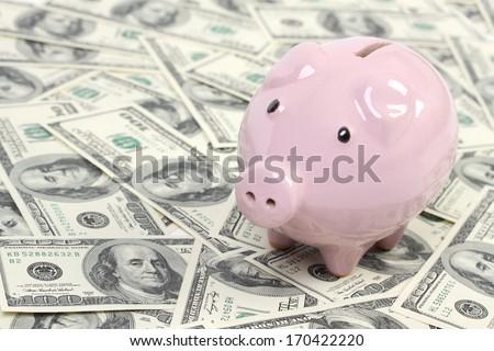 Piggy bank style money box on background with money american hundred dollar bills - stock photo