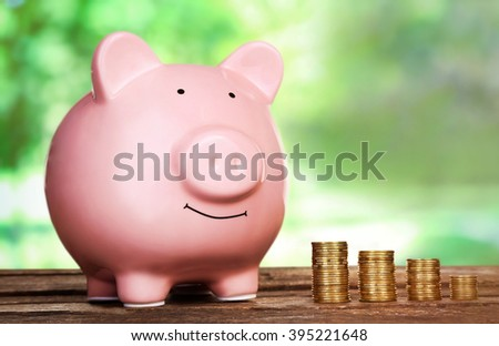 Piggy bank style money box on wooden table on bright background - stock photo