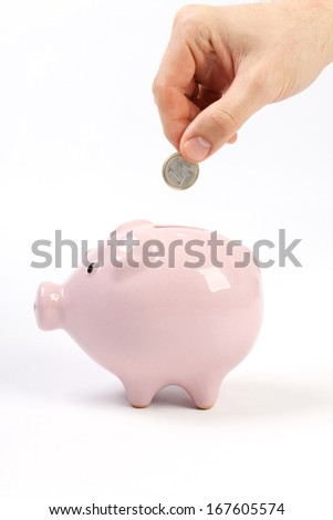 Piggy bank style money box with one euro falling into slot on white background