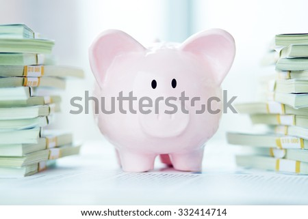Piggy bank surrounded by stacks of dollar bills - stock photo