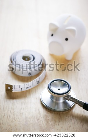 Piggy bank, tape measure and stethoscope - stock photo